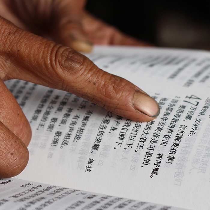 Finger on an open Chinese Bible